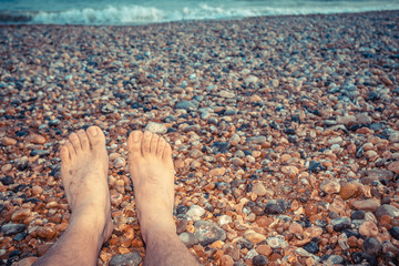 The feet of a young man sitting on the beach