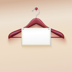 Wooden  hanger with tag isolated on cream background.