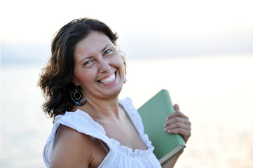 happy attractive 40s mature woman holding book smiling