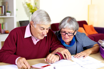 Happy senior couple at home calculating debt