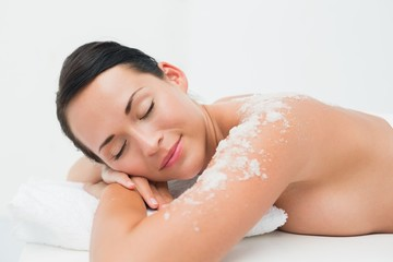 Peaceful brunette lying with salt scrub on shoulders