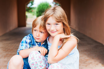 Outdoor portrait of adorable kids sitting in a tunnel