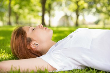 Pretty redhead lying on grass relaxing