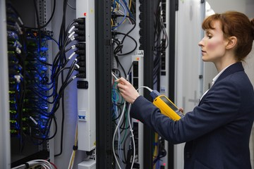Technician using digital cable analyzer on server