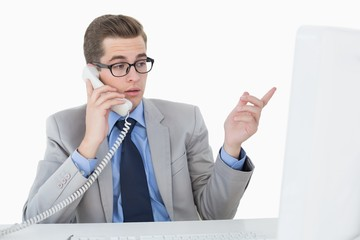 Nerdy businessman working on computer talking on phone