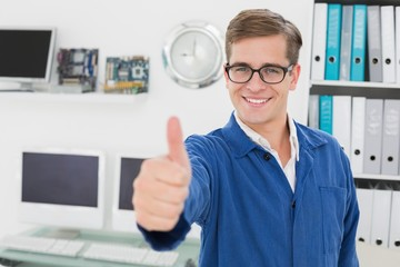 Smiling technician looking at camera showing thumbs up