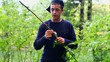 Teen with a knife cuts the branch in the forest