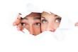 Young couple peeking through torn paper