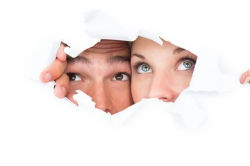 Young couple peeking through torn paper