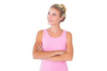 Pretty young blonde in pink looking up with arms crossed