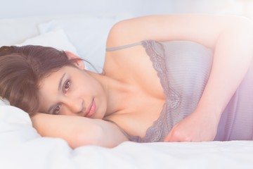 Beautiful brunette lying on bed smiling at camera