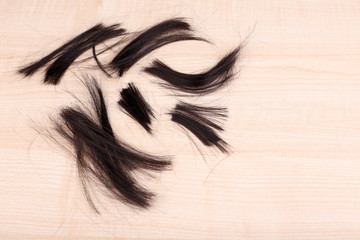 Cut hair on wooden background