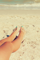 Girl feet in the sand on the beach in summer