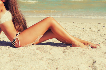 Girl feet in the sand on the beach in summer