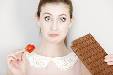 Woman deciding between sweet and fruit