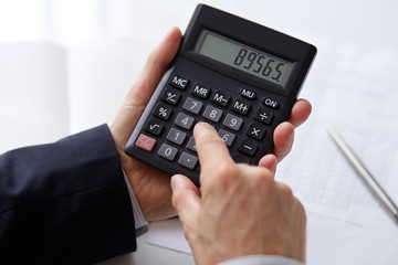 Men's hands with calculator