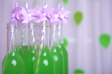 Bottles of drink with straw on decorative background