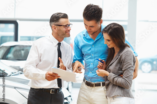 Young Couple Signing a Contract  in Car Showroom. - 68844775