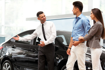 Сar Salesman Invites Customers at Showroom.