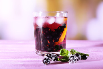 Glass of cold berry cocktail with lemon on wooden table