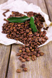 Coffee beans on piece of paper on wooden background
