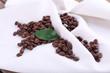Coffee beans on white napkin on wooden background