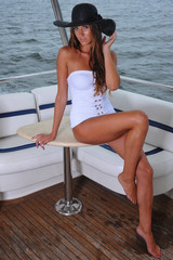 Glamor young woman posing on the luxury yacht.