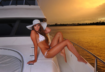Swimsuit model wearing bikini and hat posing on the  yacht.