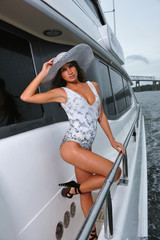 Sexy brunette model posing on the luxury yacht.