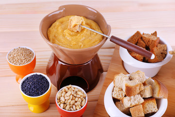 Fondue, little bowls of spice, rusk and biscuits
