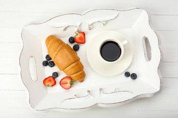 Delicious breakfast with coffee, fresh croissant and berries
