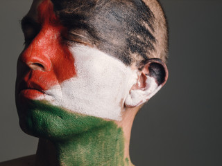 Man with his face painted with Palestinian flag