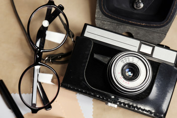 Retro camera on table with glasses and sheets of paper