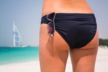 Sexy back of a beautiful woman in bikini on the beach