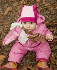 Годовалый ребёнок сидит на земле
