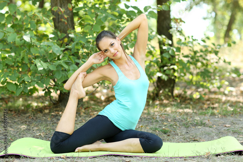 canvas print picture Young beautiful woman doing yoga exercises in park