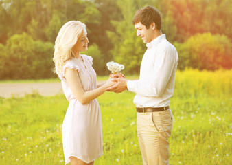 Happy smiling couple holding bouquet of wildflowers