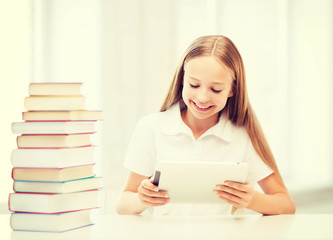 girl with tablet pc and books at school