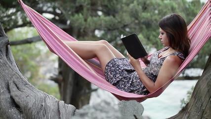 Woman in hammock on tablet