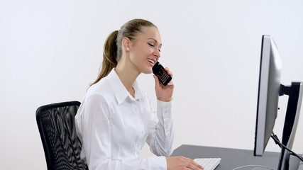 Young beautiful businesswoman typing on a computer and talking