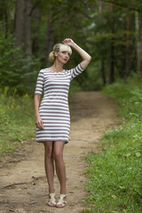 Girl walks on the wood in a dress