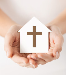 hands holding paper house with cross symbol