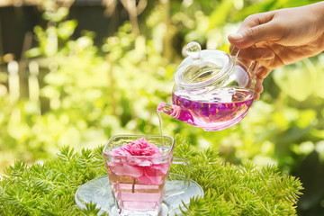 Pouring tea from a teapot into a cup in the garden