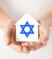 hands holding house with star of david