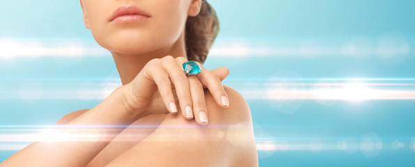 closeup of woman hand with big blue cocktail ring