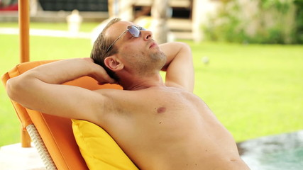 Young man sleeping on sunbed by the swimming pool