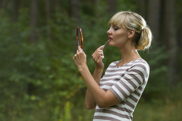 Woman looks in a mirror checking a make-up of person