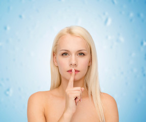 calm young woman with finger on lips