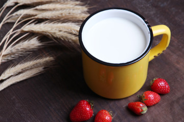 Ripe sweet strawberries in wooden bowl and mug with milk