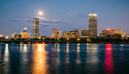Boston skyline at night with the super moon above.
